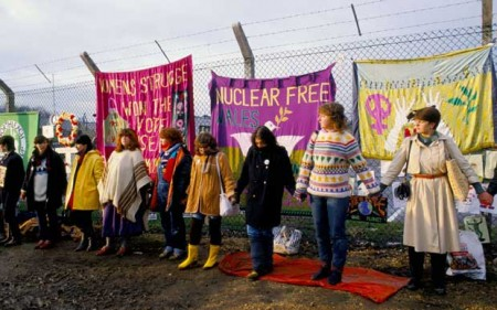 Protesters ring the Greenham Common fence decorated with handmade banners and other items (date unknown)""